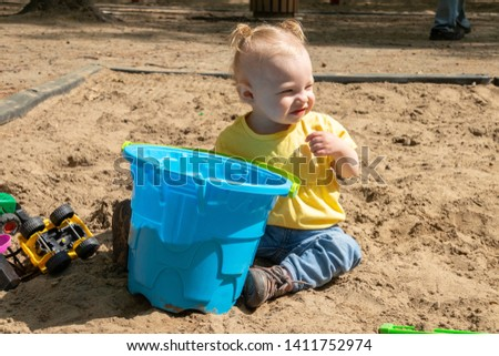 15 month old adorable blond caucasian toddler playing on sand box at the public park outdoor Sorel-Tracy Quebec Canada playing on sand box at the public park outdoor Sorel-Tracy Quebec Canada #1411752974