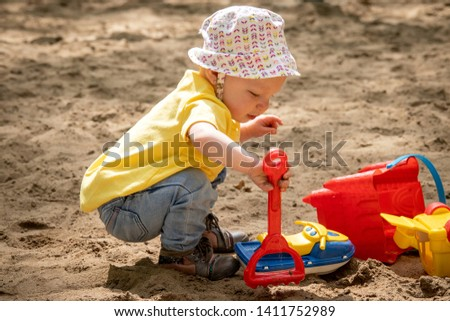 15 month old adorable blond caucasian toddler playing on sand box at the public park outdoor Sorel-Tracy Quebec Canada playing on sand box at the public park outdoor Sorel-Tracy Quebec Canada #1411752989