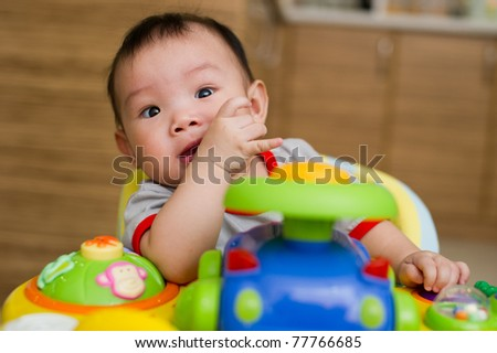 6 month old Asian baby girl chewing her fingers while sitting in a walker