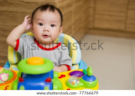 6 month old Asian baby girl smiling excitedly while sitting in a walker
