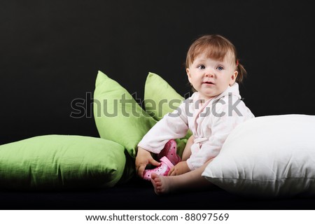 18 month old baby girl dressed in bath robe on green and white pillows on black background