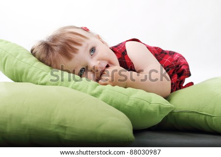 18 month old baby girl in red checked dress on green pillows on white background