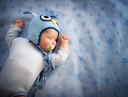4 month old baby in owl hat sleeping on blue blanket