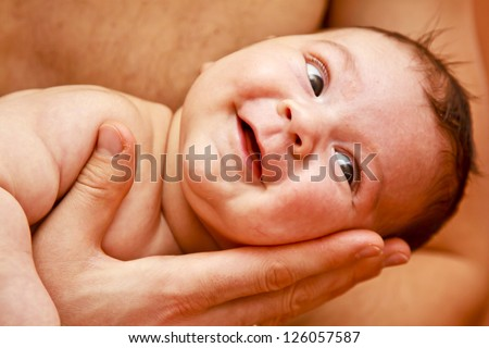 3 month old baby lying on fathers hand. First smiles