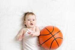 5 month old baby lying on his back on white sheet playing basketball