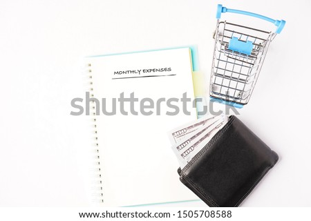 """""""Monthly Expenses"""" wordings on a notebook with wallets on the side. Flat lay composition, copy space for text #1505708588"""