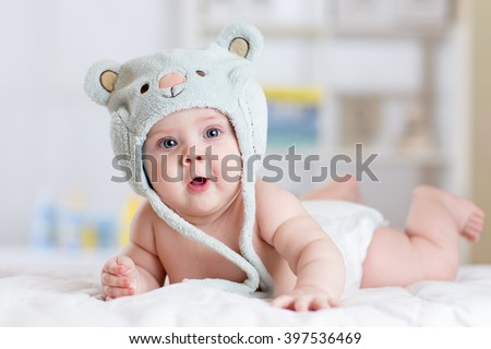 Stock Photo 5 months baby girl weared in funny hat lying down on a blanket.
