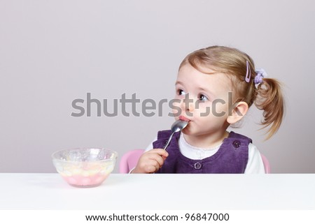 24 months old adorable little baby girl having fun while eating creamy pudding with spoon.