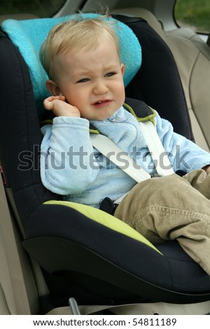 Old baby boy in car safety seat unhappy child crying stock photo