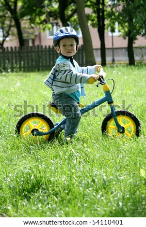 19 months old baby boy riding on his first bike in a helmet. Bike without pedals. Child learning to ride and balance on his two wheeler bike with no pedals.