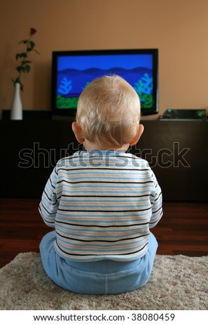 11 months old baby boy watching television - stock photo