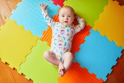 4 months old baby girl lying on colorful play mat on the floor. Activity carpet for kids