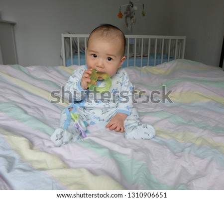 18836d6164 6 months old baby sitting on bed and biting Ice Gel Teether Ring.Portrait  Cute