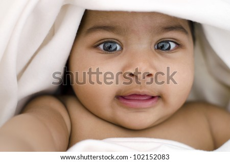 6 months old Indian baby girl smiling, lying on bed and covered by blanket