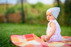 9 months old infant baby girl sits alone on garden grass in colorful blanket. Watching curiously with blue hat pink flower and summer dress. Sunny Summer day portrait