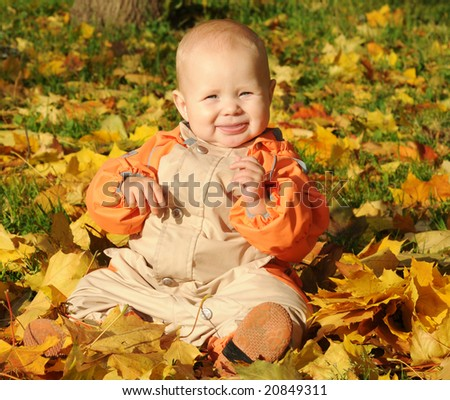 7-months Smiling Baby-girl sitting on maple leaves