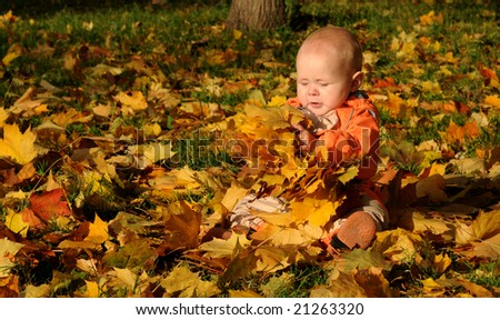 7-months Smiling Baby-girl with maple leaves on hands.