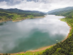 Moody Morning fog over a lake. Nature outdoors travel destination, Zavojsko lake, Stara Planina (Balkan mountain), Serbia. Aerial, drone view