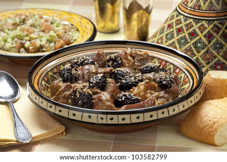 Moroccan dish with meat, plums and sesame seeds close up