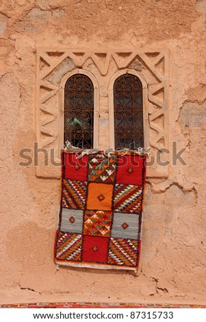 Morocco Essaouira  typical colorful Moroccan Berber carpet hanging from a beautiful window in an adobe wall