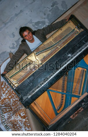 10.19.2008, Moscow, Russia. A young man standing behind an old piano. An old destroyed musical instrument close up.  #1284040204