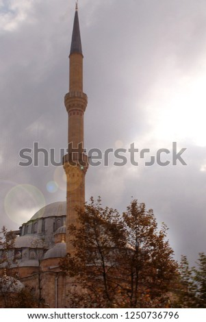 mosque with a minaret on the background of an overcast sky and a gazing sun #1250736796