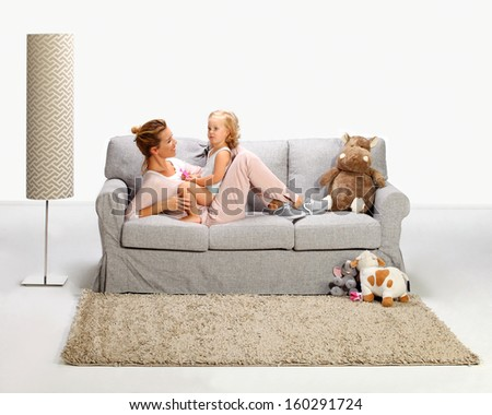 Mother and baby daughter playing on bad sofa 6