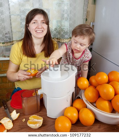mother and daughter making fresh orange juice in home kitchen