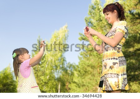 Mother together with a daughter , the digital device,  outdoor .