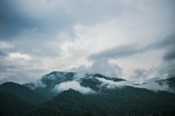 mountain top between clouds blue