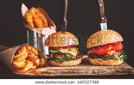 mouth-watering, delicious homemade burger used to chop beef. on the wooden table. The burgers are inserted knives.