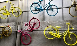Multi-colored bicycles that are randomly attached to a gray wall