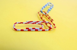multi-colored paper clips stapled together on a yellow background