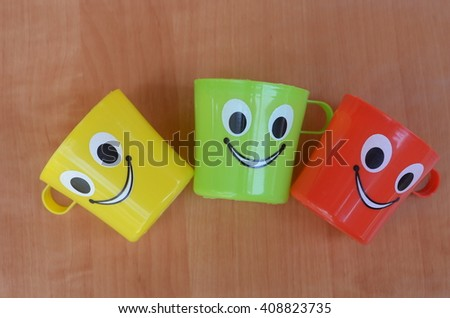 multi colored plastic kid mugs with smile symbol- Isolated wood texture  #408823735