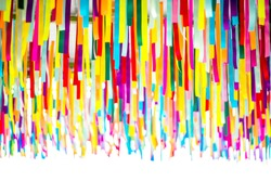 Multi-colored ribbons hanging from the ceiling. Bright and colorful color background.party back ground.congratulations. Fun in the party. The background is bright like a rainbow.
