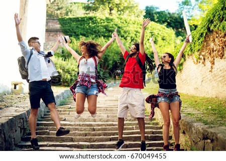 Multiracial couples exploring a city, happy tourists discovering new locations jumping in the air.. #670049455