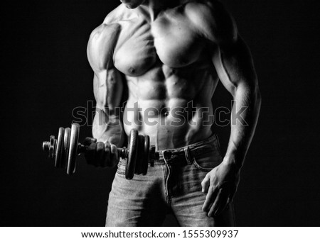 Muscular man lifting weights. Black background.  Stock foto ©