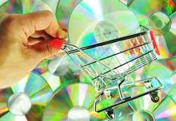 Music shopping concept with hand holding a shopping cart and music CDs or DVDs