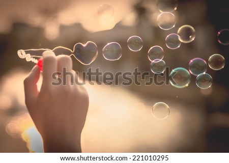 My Heart Bubbles at the sky, sunset,Love in the summer sun with bubble blower,romantic inflating colorful soap bubbles in park stock photo