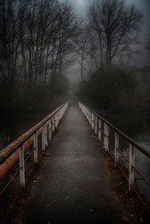 mystical bridge in the park is shrouded in fog