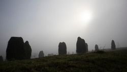 Mystique sheaves of hay at dawn in the countryside , sun through the fog