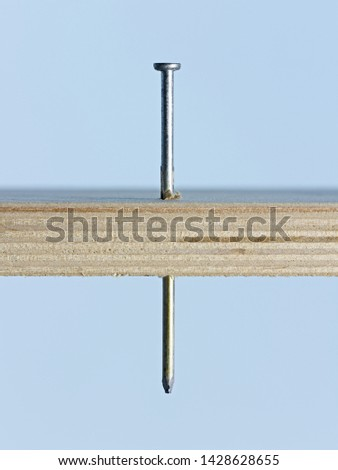"""""""Nailed it"""" conceptual image of simple, graphic nail through wood board on blue background #1428628655"""