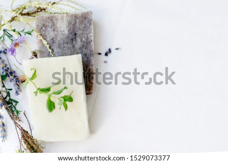 Natural soap with herbs for skin care on a white background, top view, copy space