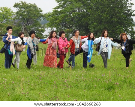 22nd of July 2016 - Group of Chinese women standing in line on a grass field posing for a photo, Kizhi Island, Russia        - Shutterstock ID 1042668268