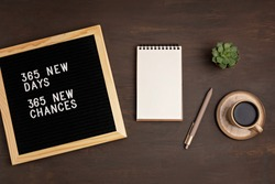 365 new days, 365 new chances. Letter board with motivational quote on dark wooden background with notepad , pen, coffee and succulent. New year's resolutions mockup. Flatlay, top view