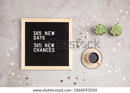 365 new days, 365 new chances. Letter board with motivational quote on grey concrete background with coffee cup. New year resolutions and goal setting, self improvement and development concept.