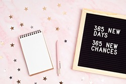 365 new days, 365 new chances. Letter board with motivational quote with notepad , pen and stars confetti. New year's resolutions mockup. Flatlay, top view
