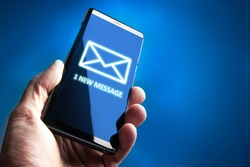 1 new message. Phone in the hand of a man. Concept - man received an SMS message. Human received a new message in messenger. Concept - sending SMS messages. An envelope is drawn on the phone screen