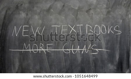 """New textbooks, no more guns"" sign written by a child on a chalkboard #1051648499"