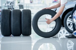 4 new tires that change tires in the auto repair service center, blurred background, the background is a new car in the stock blur for the industry, a four-wheeled tire set at a large warehouse